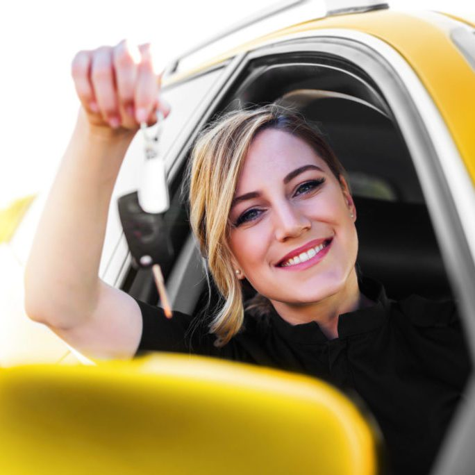 An attractive woman in the yellow car holds a car key in her hand. Rent or purchase of auto - concept.