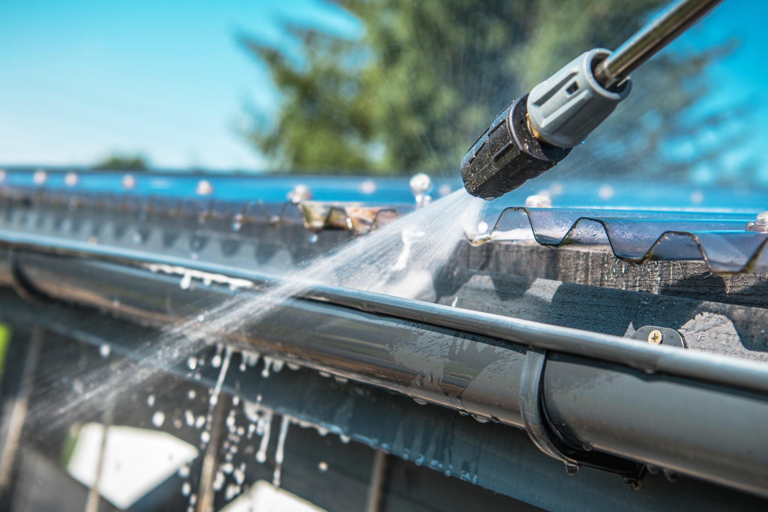 Spring Rain Gutters Cleaning Using Pressure Washer. Closeup Photo.