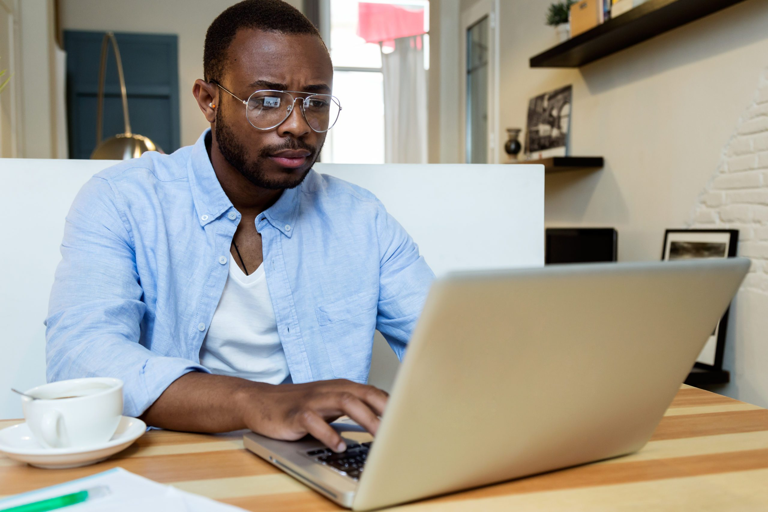 Portrait of handsome young black man working with laptop at home.