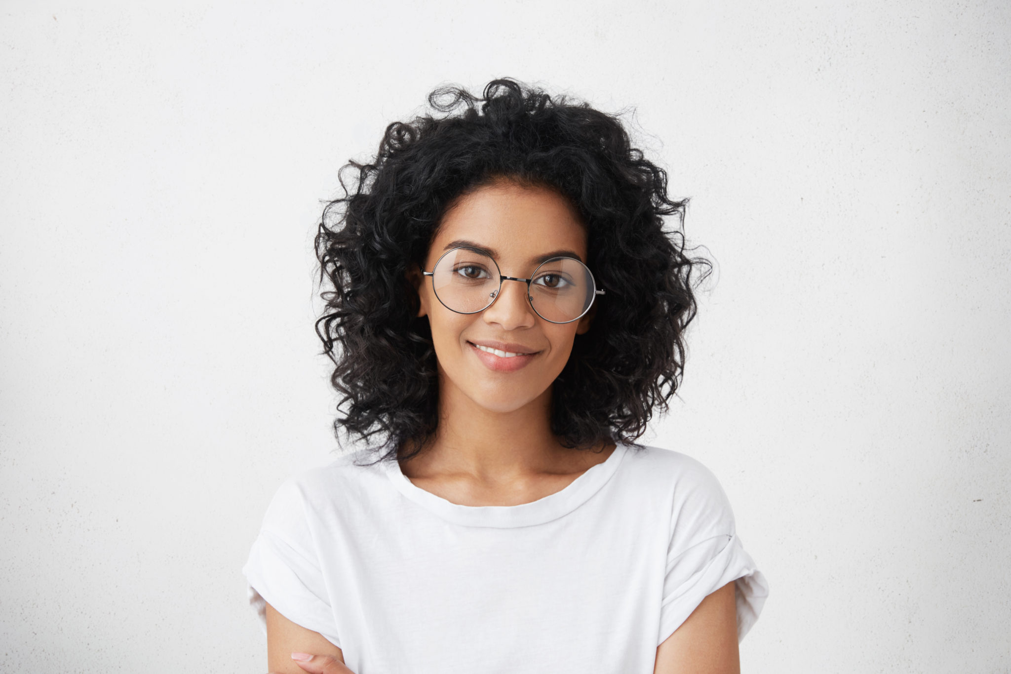 Close up studio shot of beautiful young mixed race woman model with curly dark hair looking at camera with charming cute smile while posing against white blank copy space wall for your content
