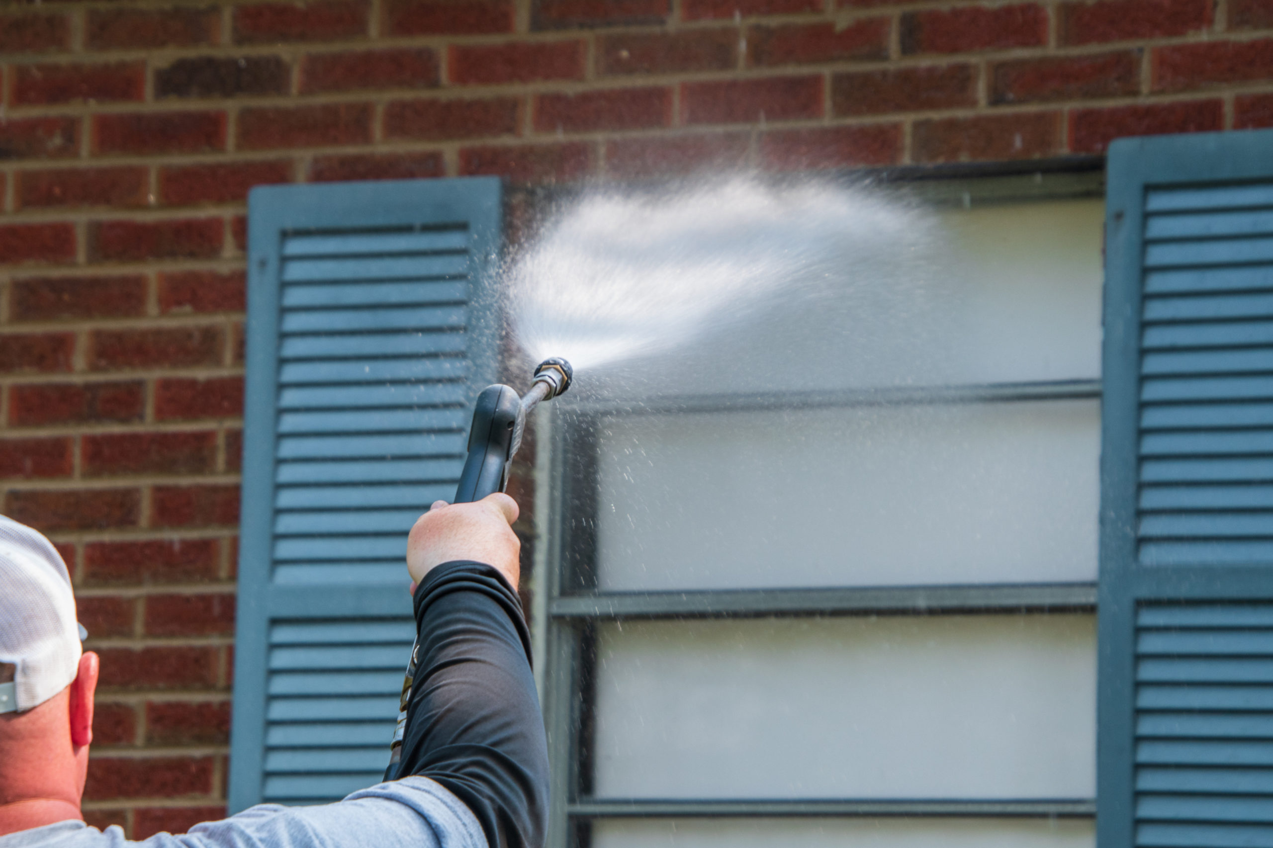 Arm and hand holding a sprayer aimed at a window that has a blue shutter on a red brick wall. The nozzle is spraying a wide water on the window